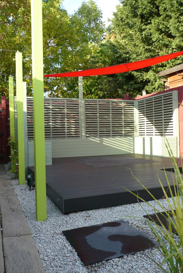 A new dark grey composite decked area with fitted seating and a bright red sail shade; a paved centre to the deck is to allow for a fire pit to be set there. The upright posts both support the shade and form an arch for climbers to the left hand side.