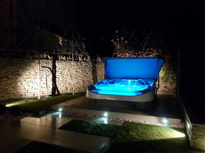The garden at night; the hot tub is the central wow factor, but the soft garden lighting complements it.