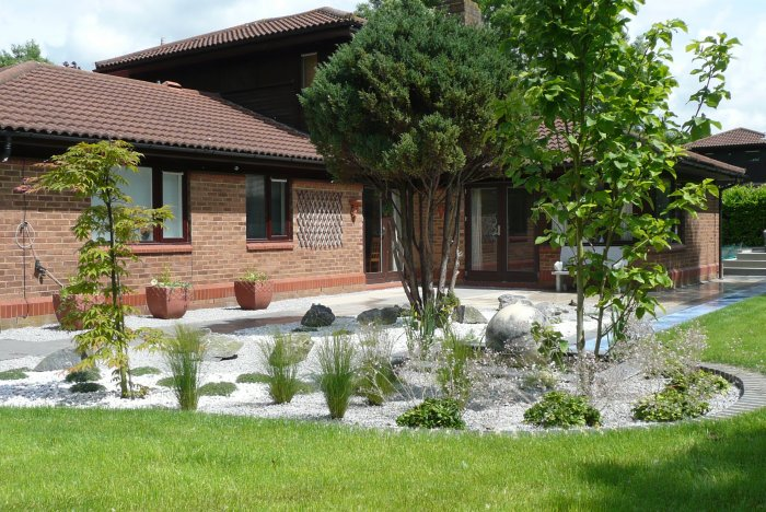 The new garden; a softly coloured porcelain patio seeps round the house, framed with planting and gravel areas.