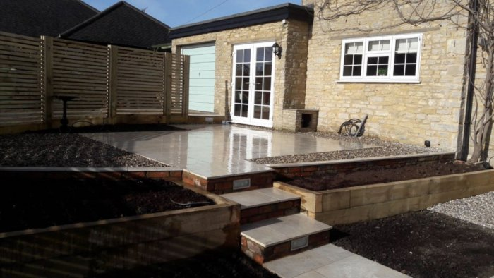 The garden now had improved and simpler levels; Bradstone external porcelain mixed with timber is a soft palette against the stone of the house.