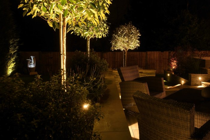 A night time view across the garden shows the lit up water feature in the lower garden.