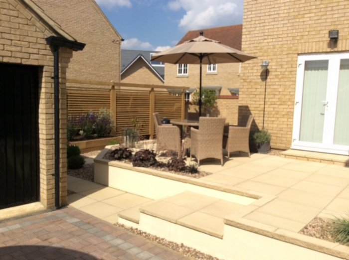 The view of the new patio; rendered walls soften the look, the paving is chosen to withstand the shady aspect of a lot of this garden.