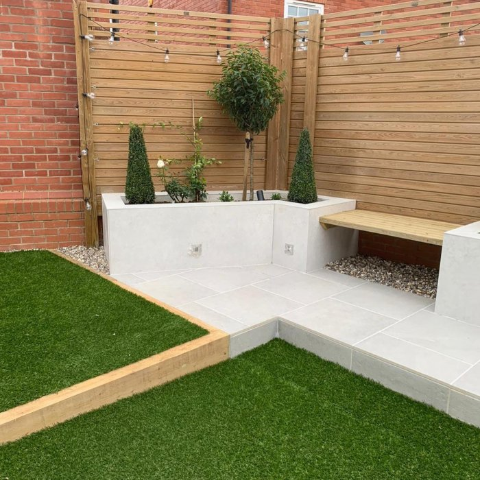 The paving and raised bed cladding is all in London Stone external porcelain in 'Florence Grey'. Raised beds frame a small fitted bench.