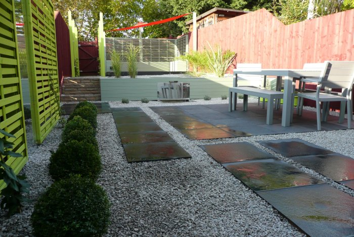 The completed garden; just seen to the left is trellis is a citrus green that frames a large mirror; the paving is broken up with areas of gravel to add interest. The planting is very simple and contemporary.