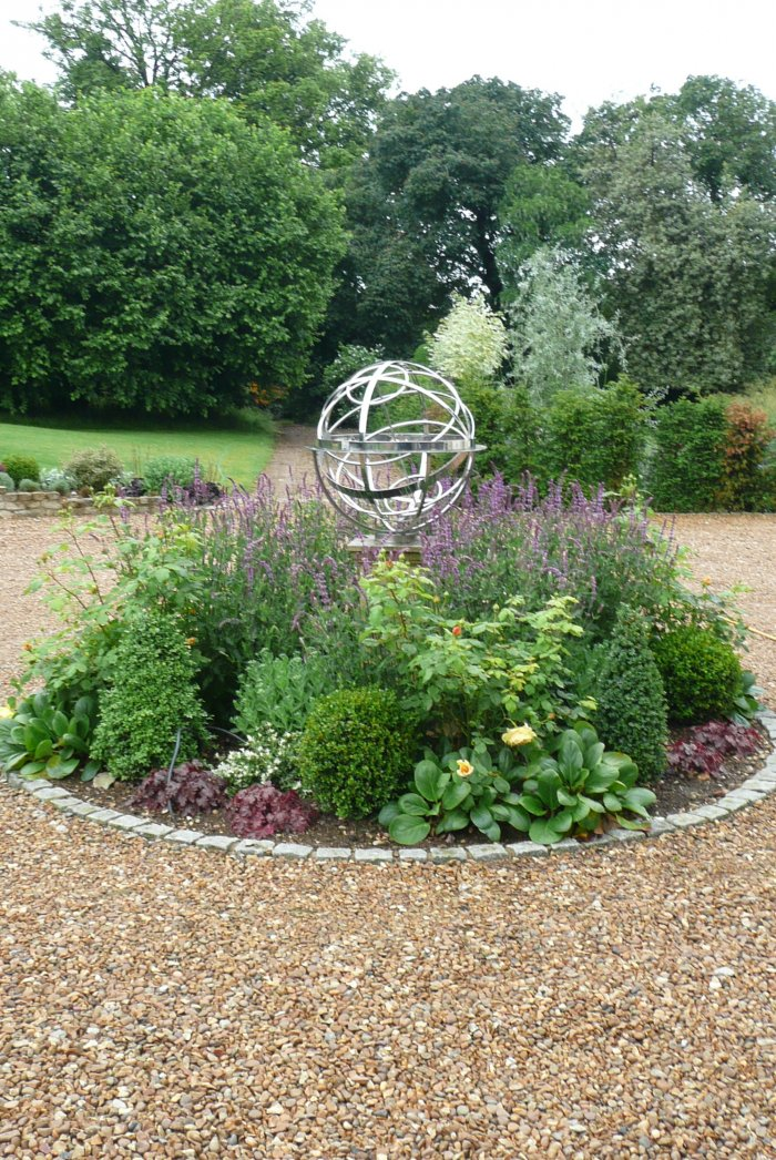 A formal central bed with clipped Buxus and roses and a beautiful sundial.