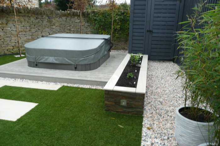 The decking surround is composite decking; a clad low raised planter adds interest and defines a gravel path to the screened oil tank area.