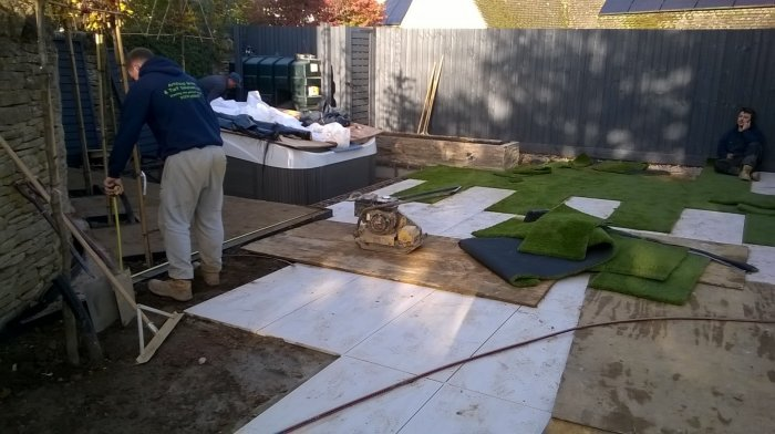 The artificial grass being laid and the porcelain paving now in place.