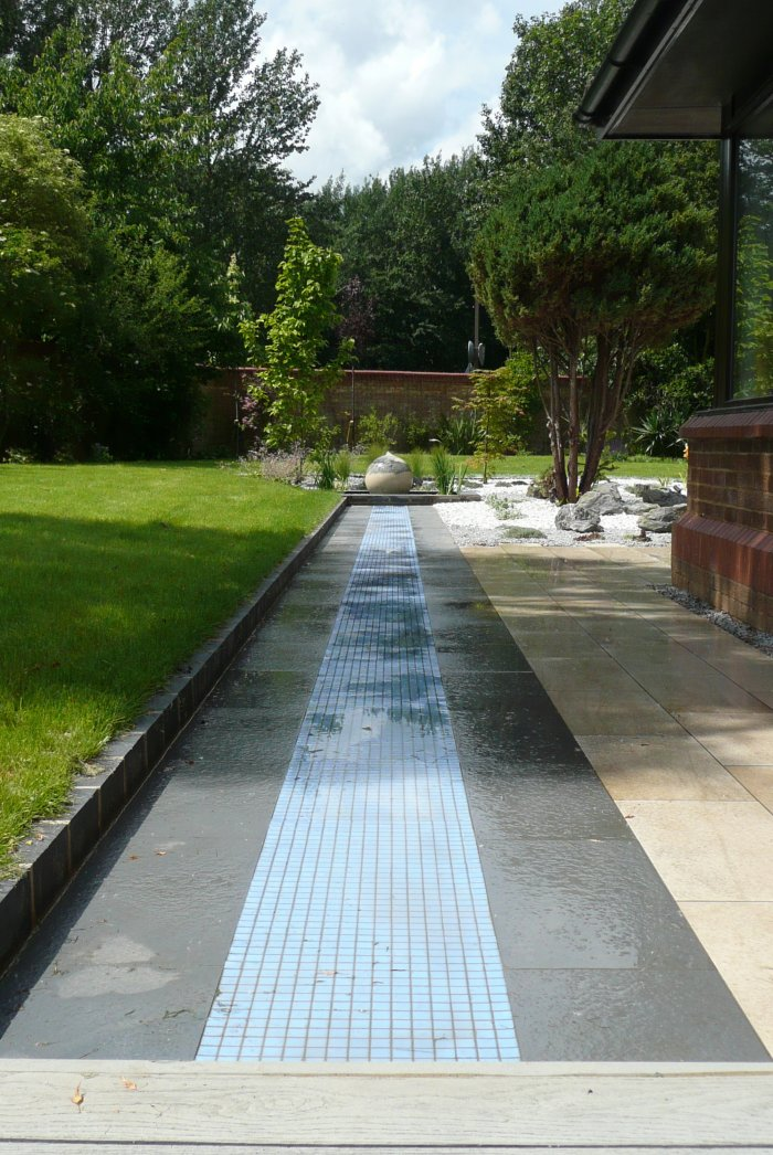 The tiles in the rill glow in the dark and link the lit up infinity edge hot tub to the water feature.