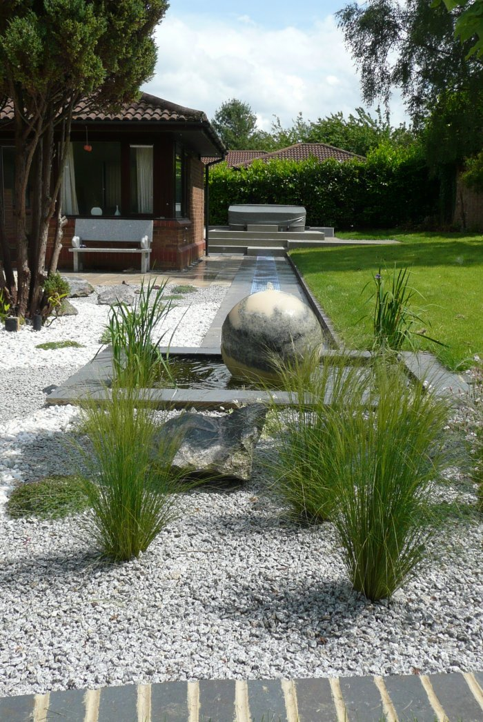 A marble sphere sits on a shallow pool as a water feature, it is linked by a tiled rill.