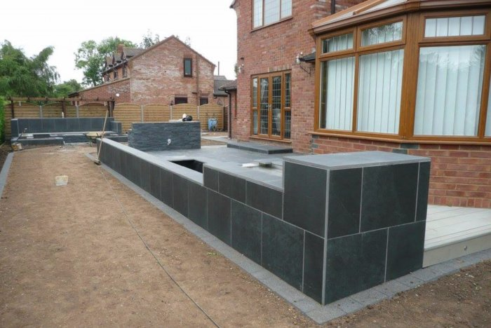 A tiered water feature clad in the paving, a new patio and a decked area around the conservatory allowing a flush transition to this area.