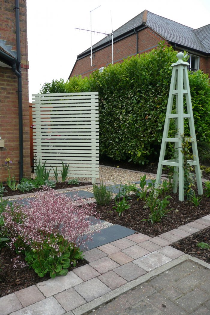 A trellis panel and obelisx add height and screening; painted a pretty colour to complement the house.